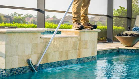 Technician Scrubbing Side of Spa | Edgewater Pools and Spa Services - Naples, Bonita Springs, Isles of Capri, & Estero